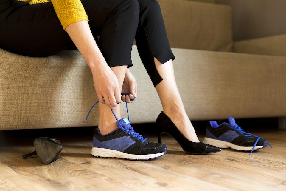 Kvinne bytter ut stiletthæler med joggesko