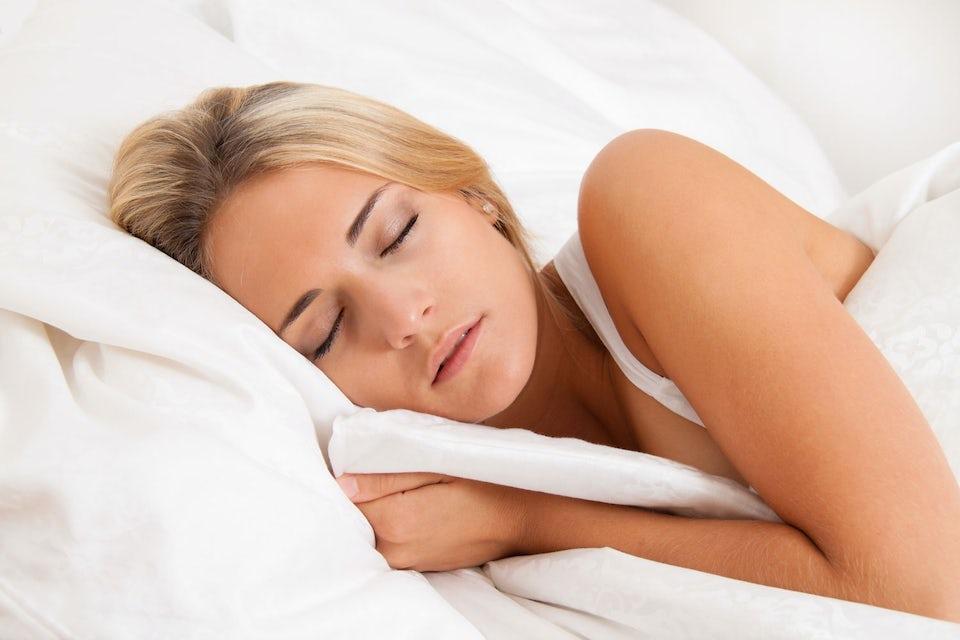 kvinde sover i hvide dyner