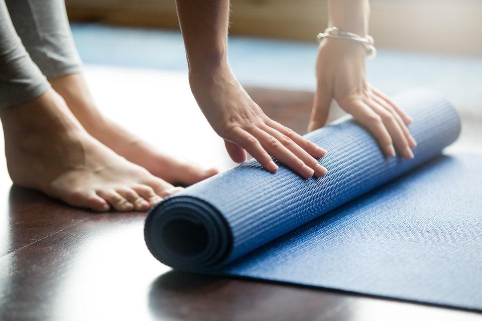 Kvinne ruller sammen en yogamatte