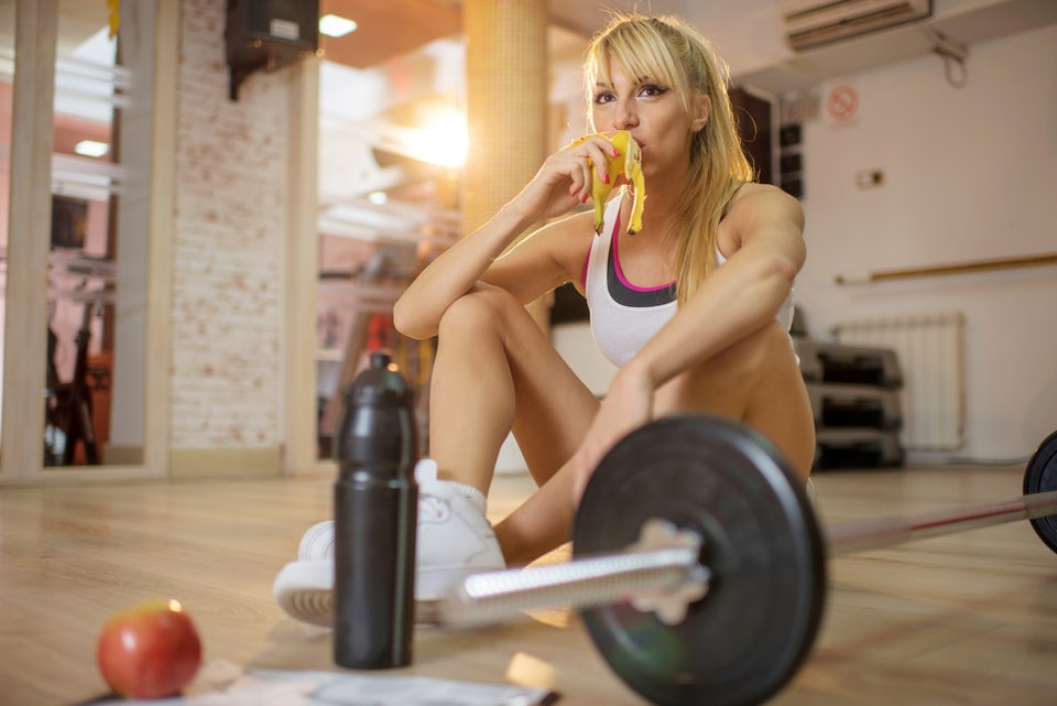 Atletisk kvinne spiser proteinrik snack