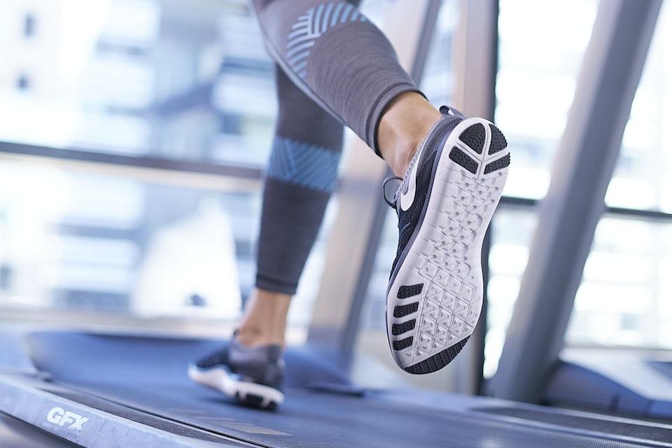 Nainen juoksee juoksumatolla, kuva kengänpohjasta
