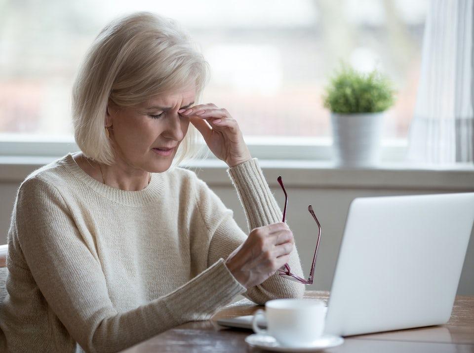 Muskeltics – kvinna har ryckningar i ögonlocket och sitter och gnider sig i ögat