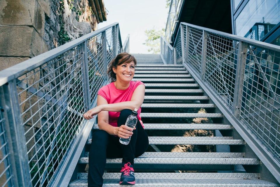 Kvinne sitter i trappa med en vannflaske i hånda