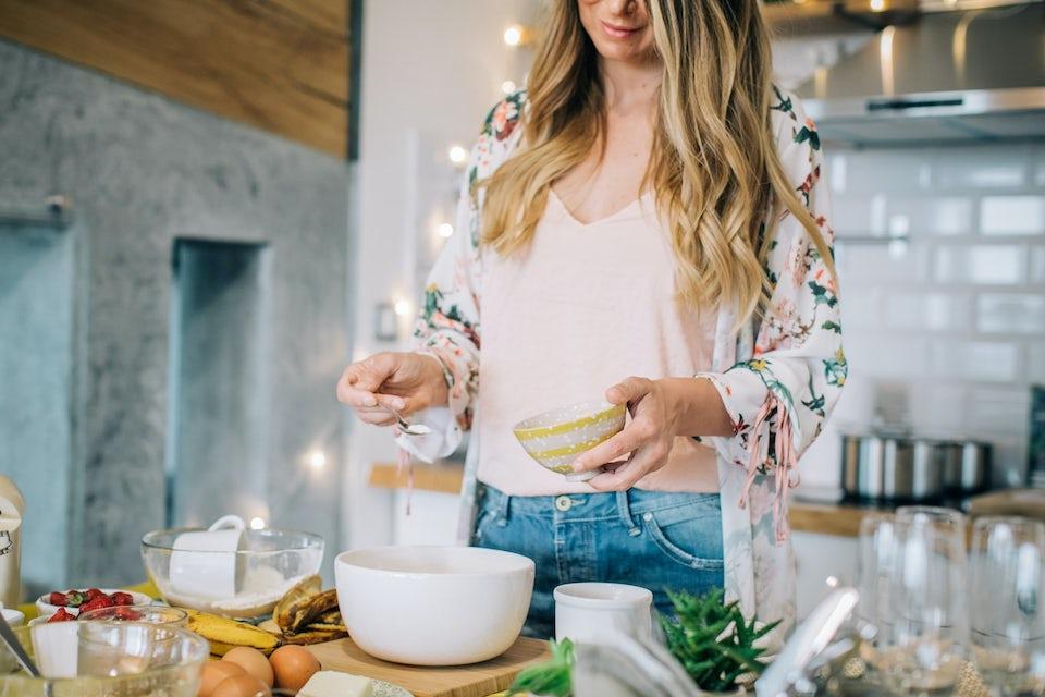 Kvinna står i köket och lagar mat