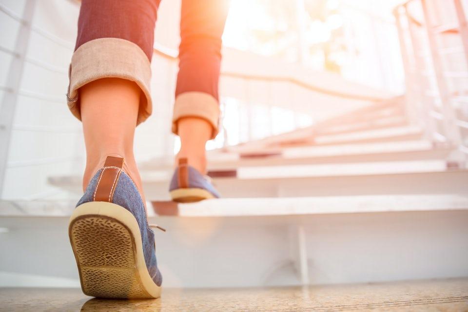 Kvindefødder på vej op ad trappe