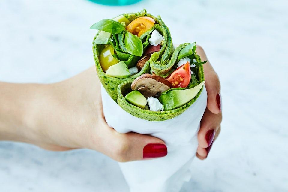 Kvinnehånd holder en grønn wrap med sjampinjong, avokado og tomater