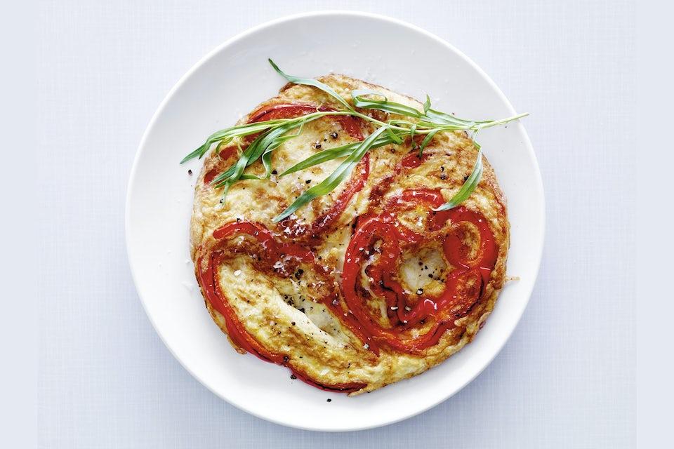 Omelett med röd paprika på vit tallrik