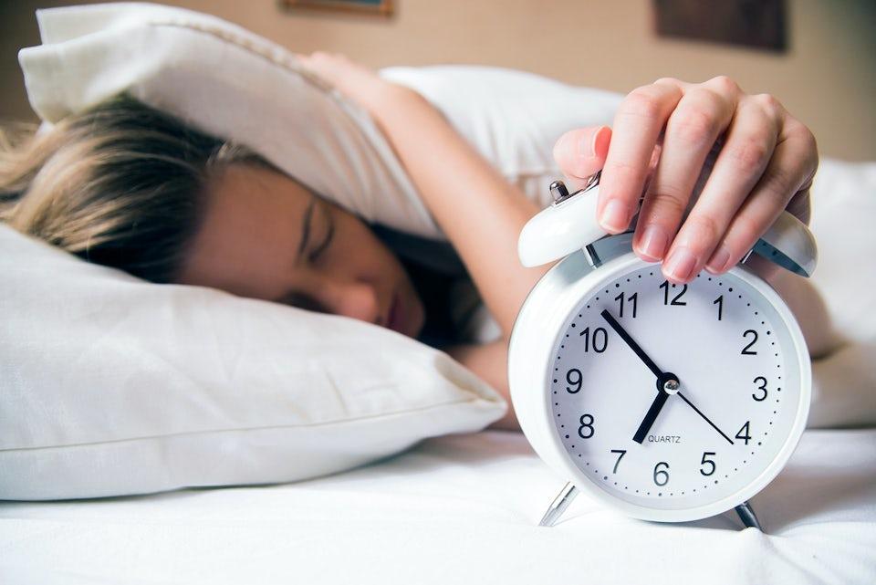 Kvinne i senga med hånda på vekkeklokka