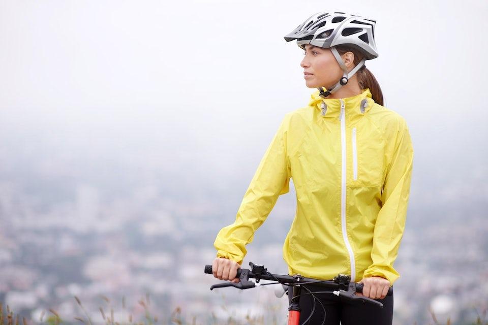 Kvinna i gul jacka på cykel och med cykelhjälm