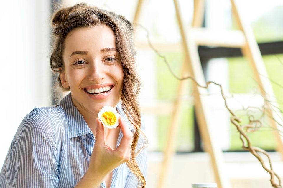 Nainen kananmuna kädessään