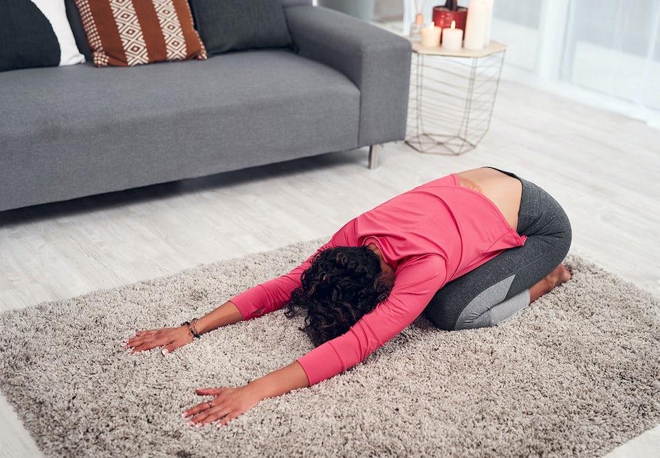 Kvinde strækker ud hjemme