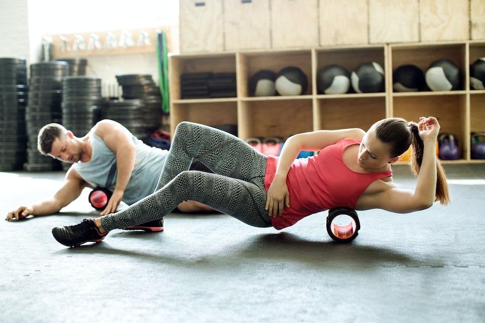 Kvinne og mann gjør øvelser med en foam roller