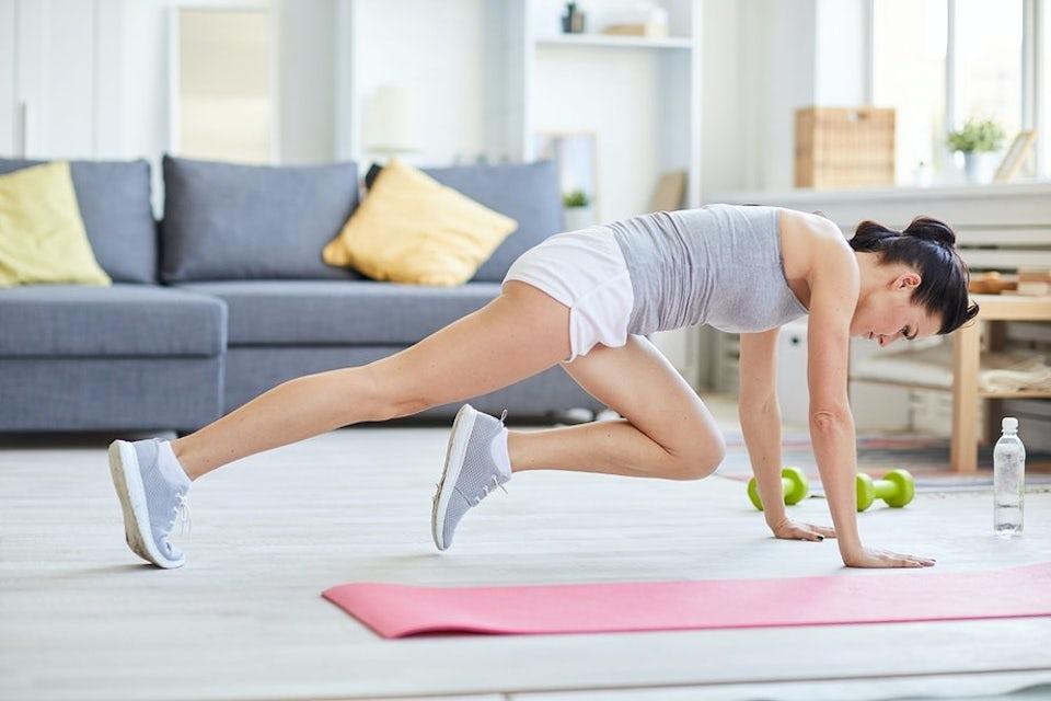 Nainen tekee kotona vuorikiipelijä-harjoitetta.