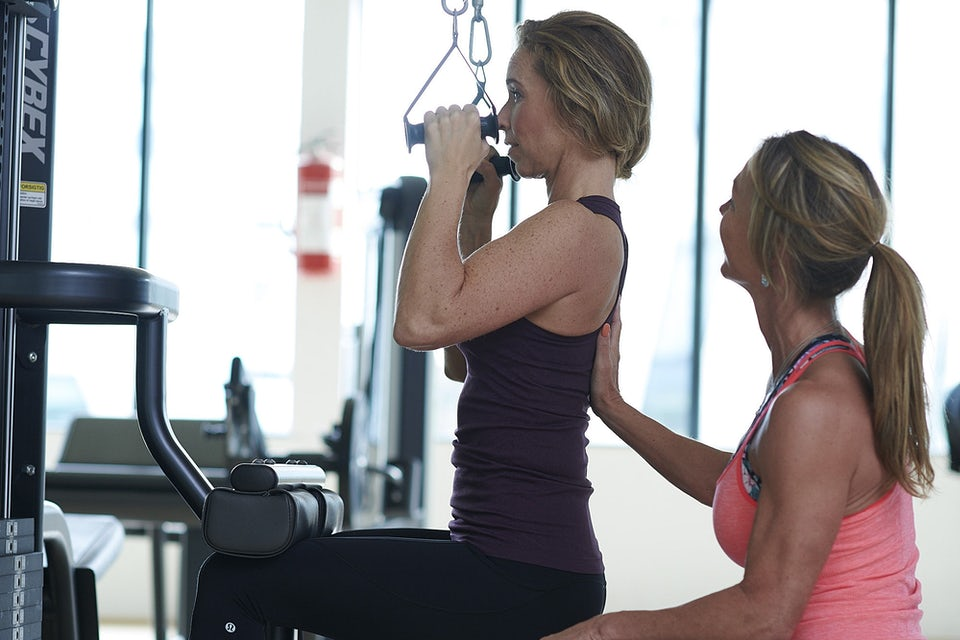 Kvinne får hjelp i styrketreningsmaskin