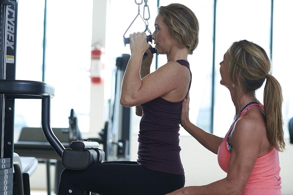 Kvinde bliver støttet i fitness