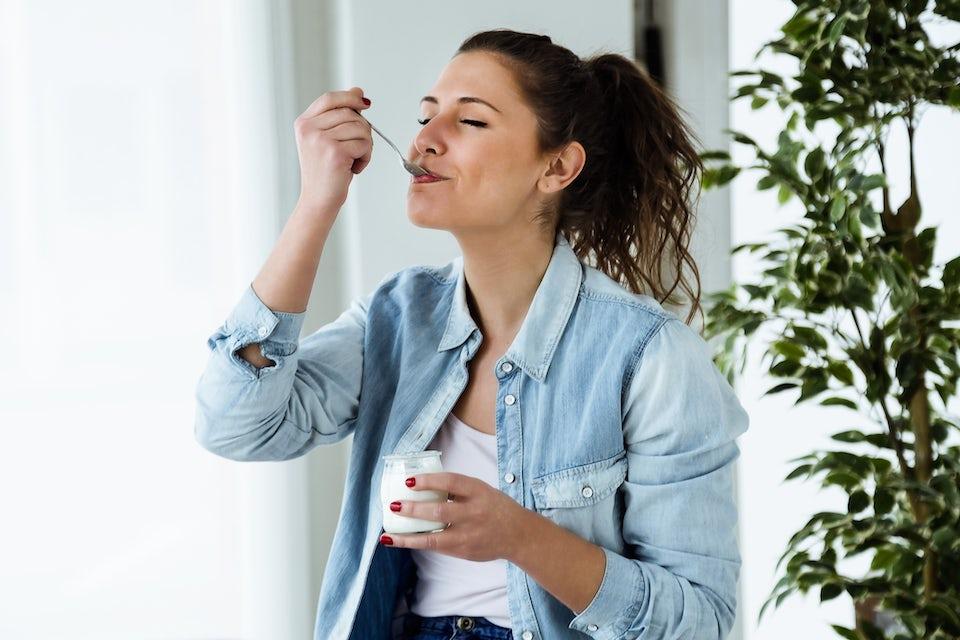 Kvinna äter yoghurt för att stärka sitt immunförsvar.
