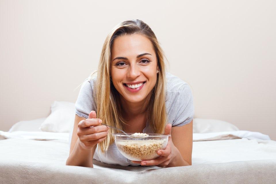 Nainen syö kauramuroja sängyssä