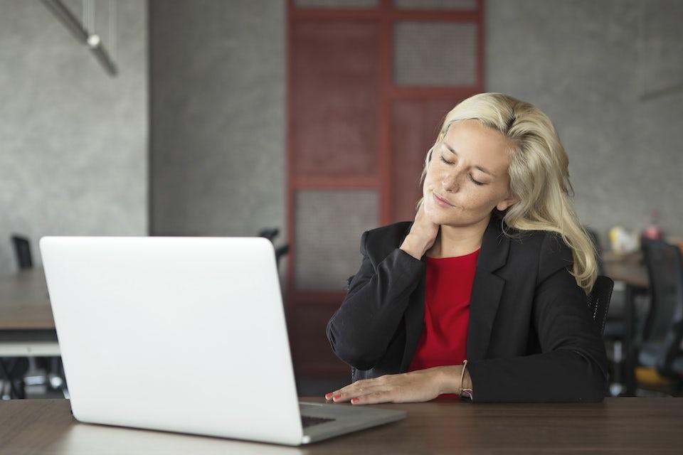 Kvinde sidder træt ved computeren