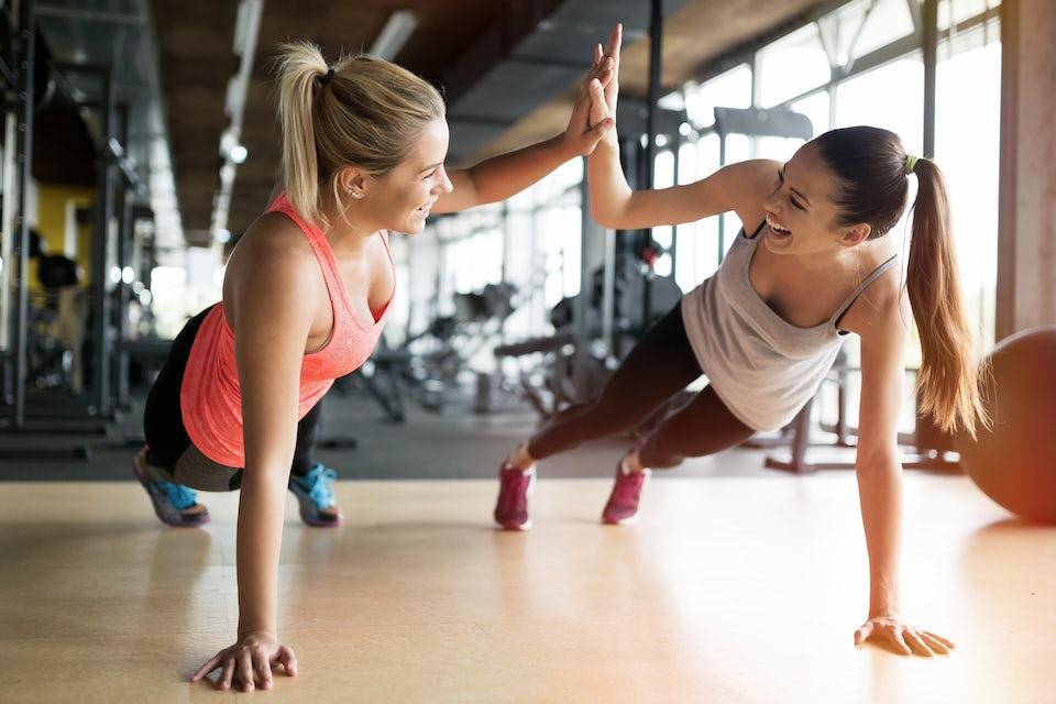 Kvinder giver high five i træningscenteret