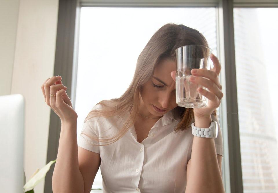 Kvinde med hovedpine holder sig til hovedet og har vandglas i den ene hånd, hovedpinepille i den anden.