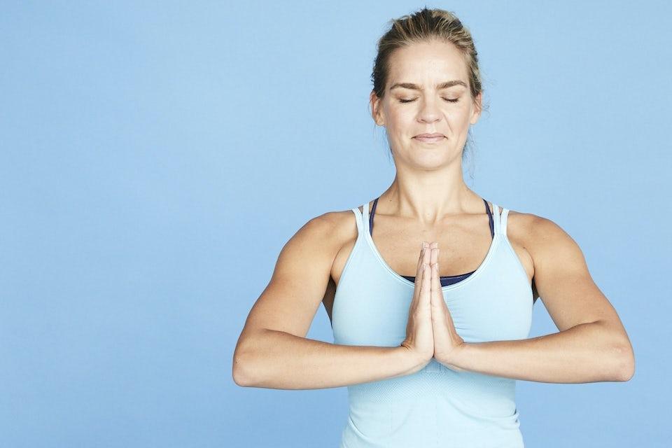 Kvinna gör andningsövning, blå bakgrund.