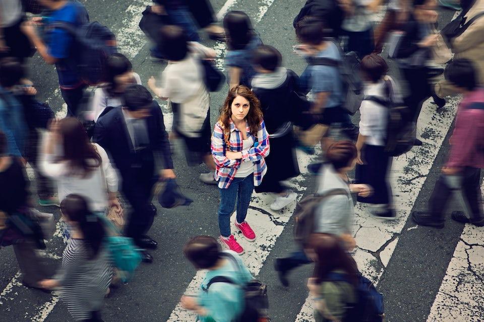 Nainen seisoo ihmisten keskellä: introvertti, ekstrovertti, ambivertti