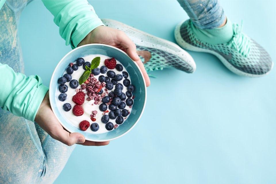 Kvinde i træningstøj spiser morgenmad