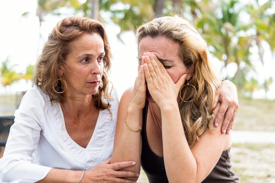 Kvinna tröstar en annan kvinna som lider av depression.