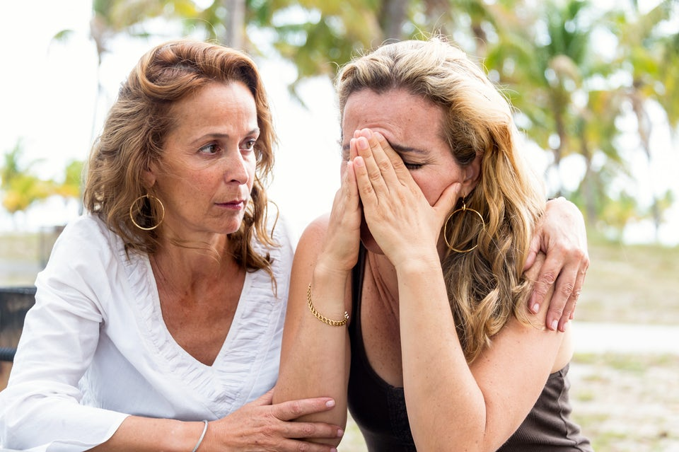 Nainen lohduttaa itkevää ystäväänsä