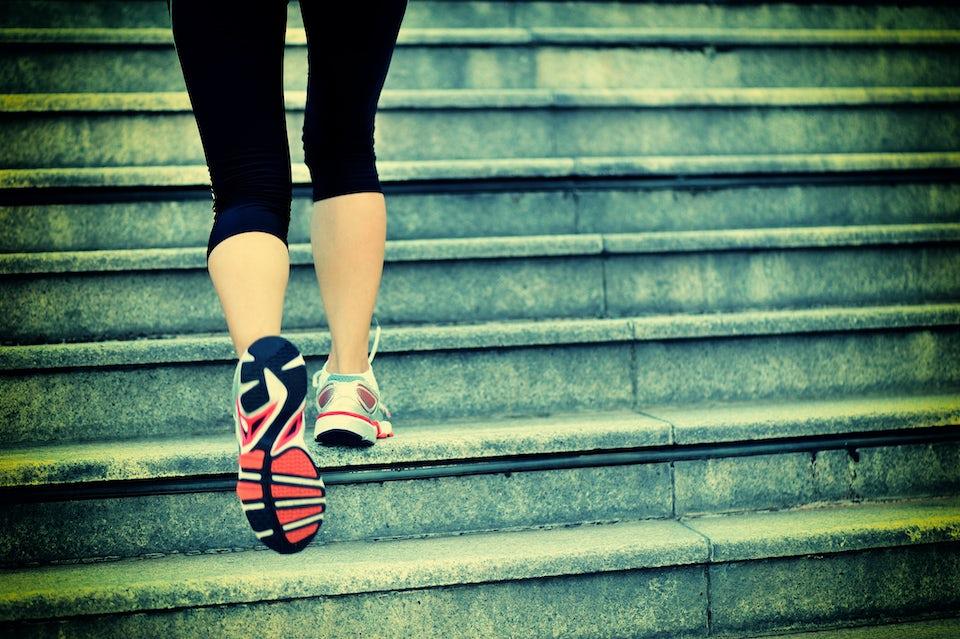 Kvindes ben på vej op af trappe.