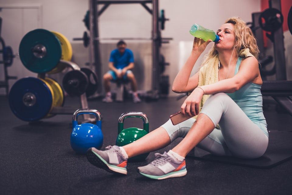 Kvinne tar pause i styrketreningen