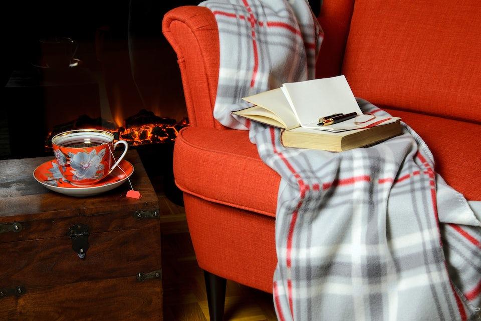 Lænestol med et tæppe, en bog og en kop te