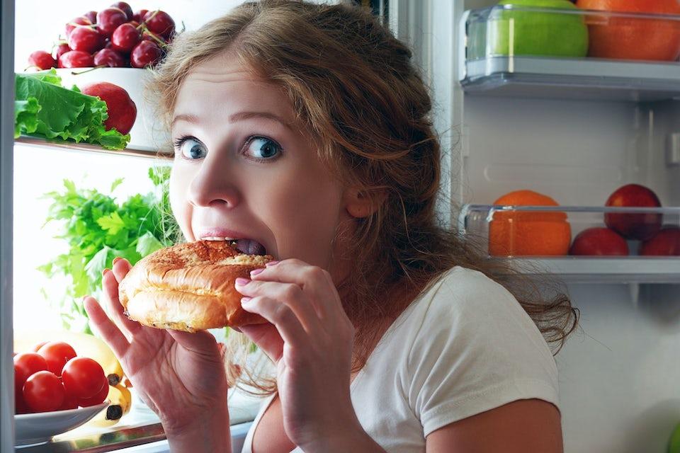 Kvinde spiser kage foran køleskab