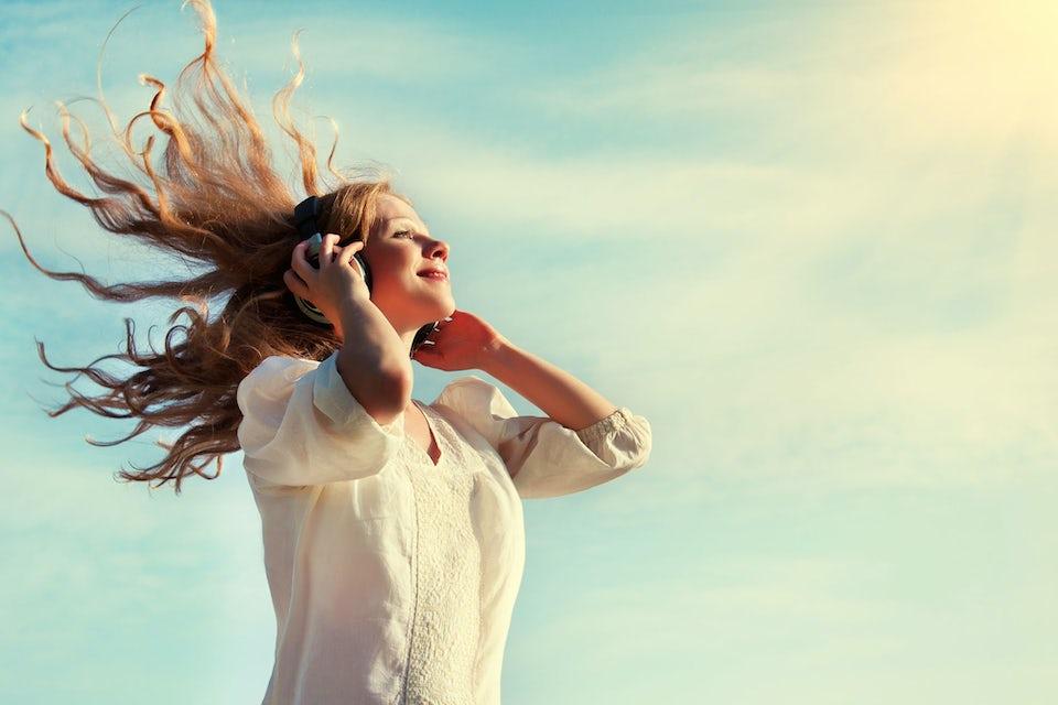 Glad kvinna lyssnar på musik utomhus – sunda tarmar.