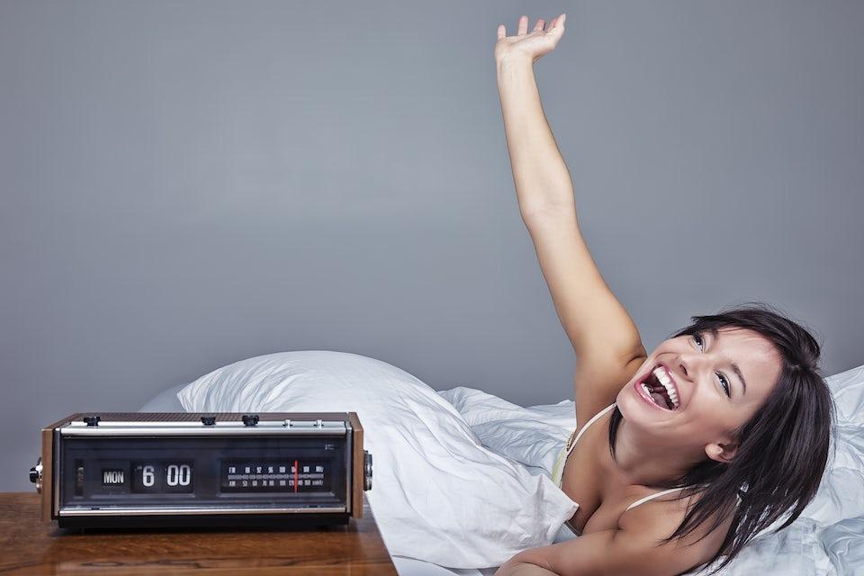 Entusiastisk kvinna vaknar upp i sin säng måndag morgon kl. 6.00.