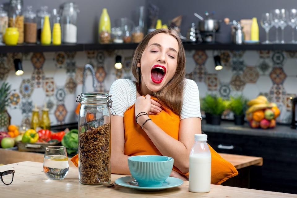 Kvinna vid frukostbord, gäspar.