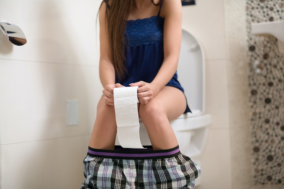 Kvinna sitter på toaletten.