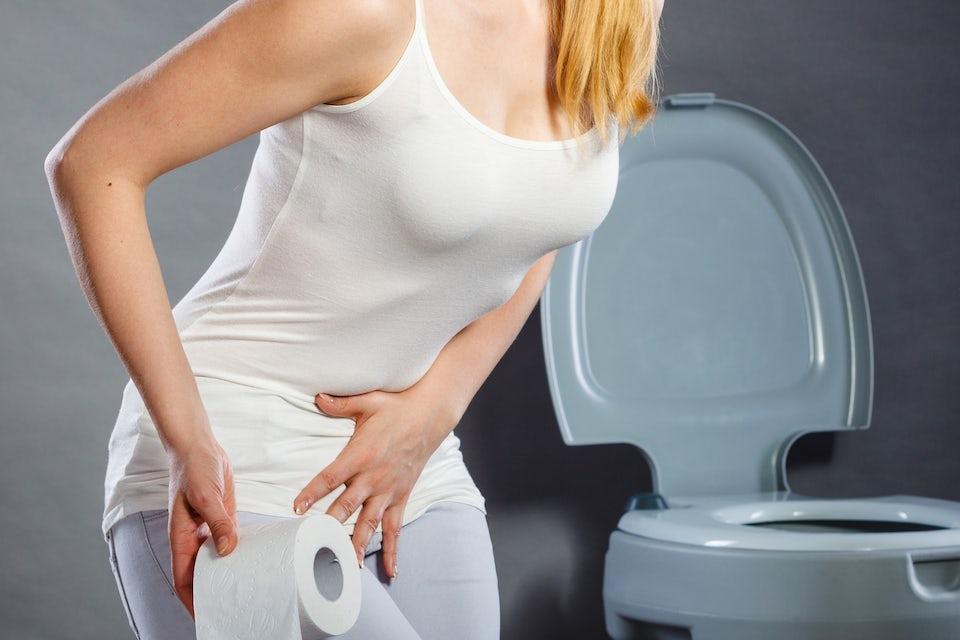 Kvinne holder seg på magen, smerter, toalett