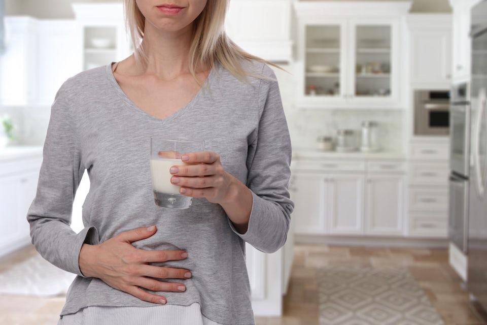 Kvinna dricker mjölk och håller sig för magen.