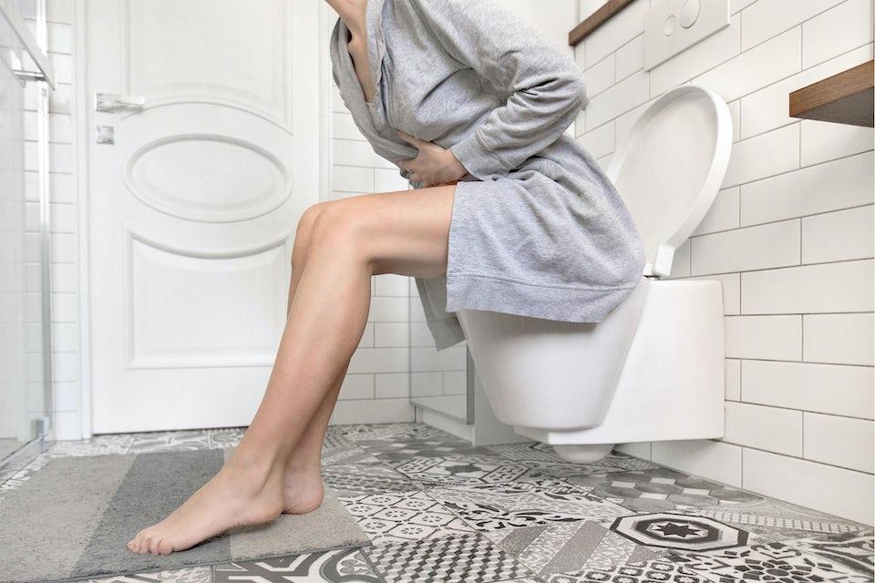 Nainen istuu wc-pöntöllä ja pitelee vatsaansa
