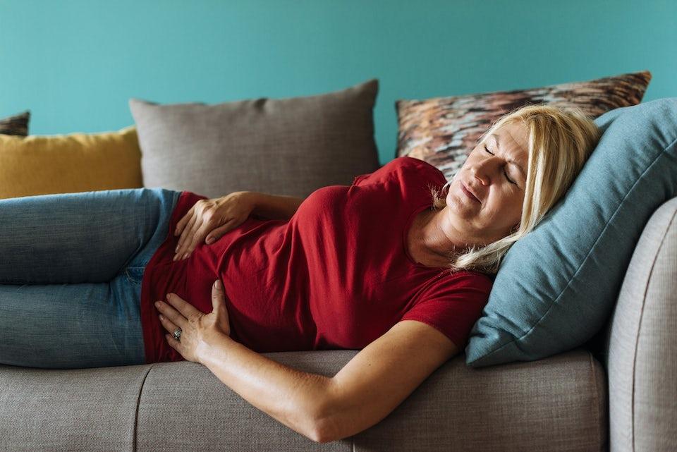 Kvinna ligger i sängen och har kramp i magen.