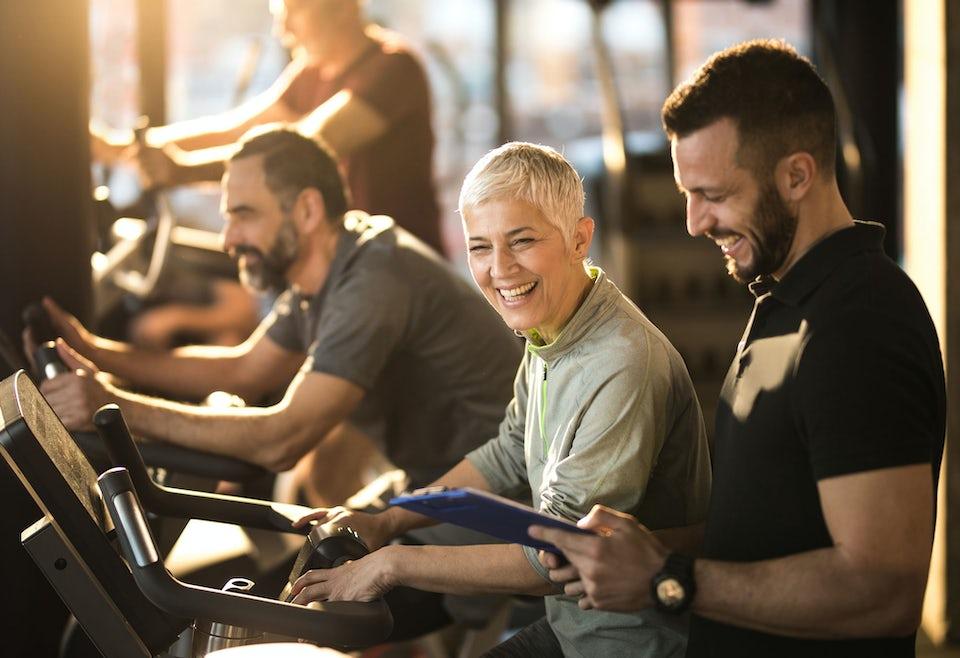 Kvinde på cykel i fitnesscenter smiler til instruktør
