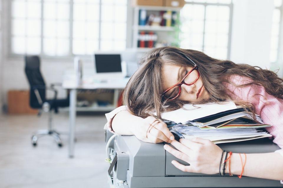 Kvinna sover på en skrivare.