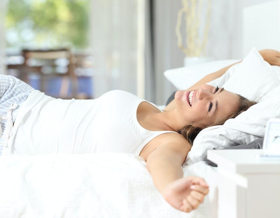 Glad kvinna ligger i sängen.