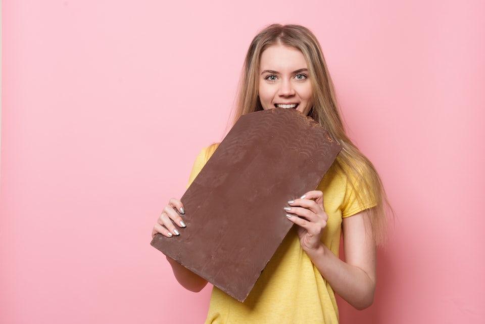 Nainen haukkaa jättimäistä suklaalevyä