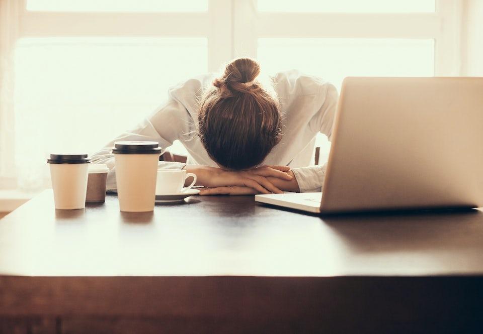 Stressaantunut nainen lepää päätään käsiinsä työpöydän ääressä.