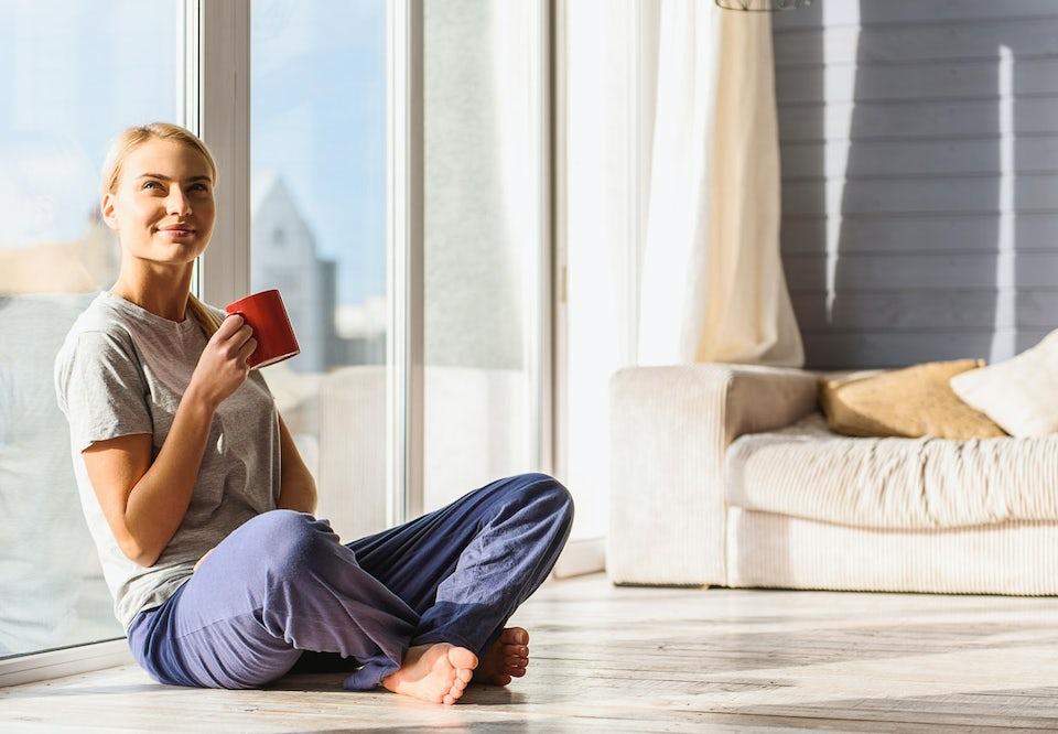 Kvinde sidder lænet op ad et vindue og drikker kaffe