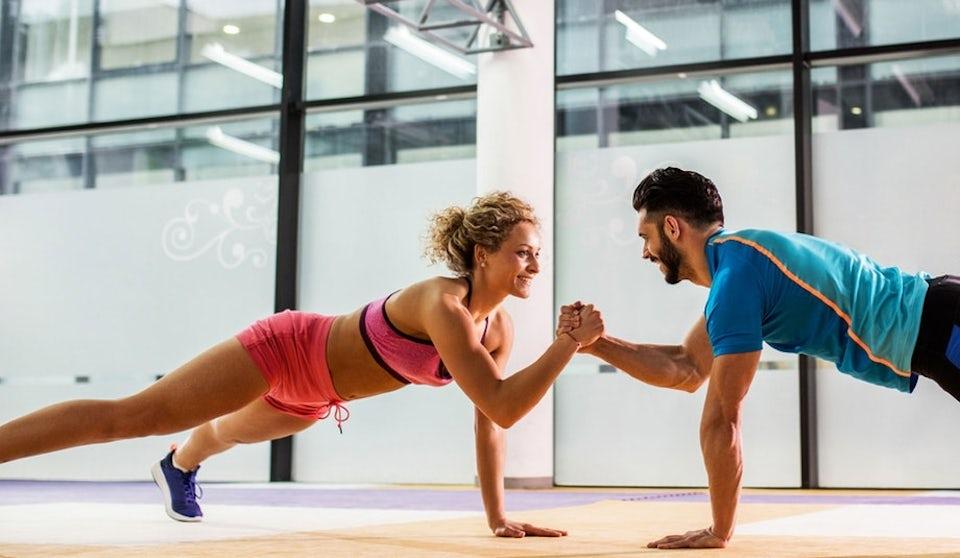 Mann og kvinne gjør armhevinger sammen på treningssenteret. Test din egen treningsmotivasjon.