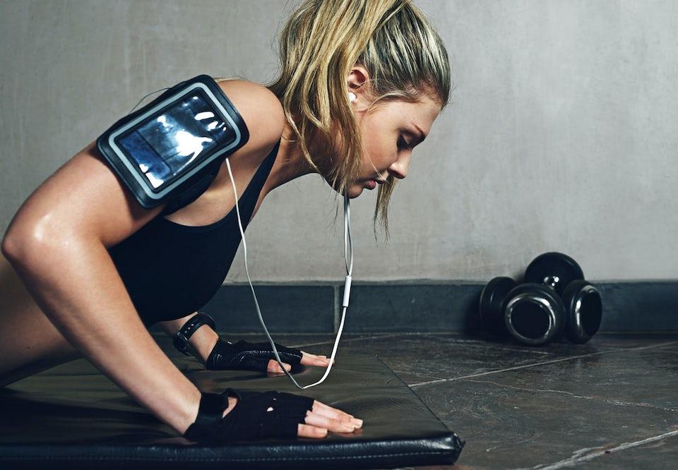 Kvinne trener på treningssenter. Hører på musikk.