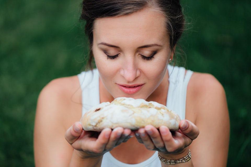 Nainen tuoksuttelee leipää